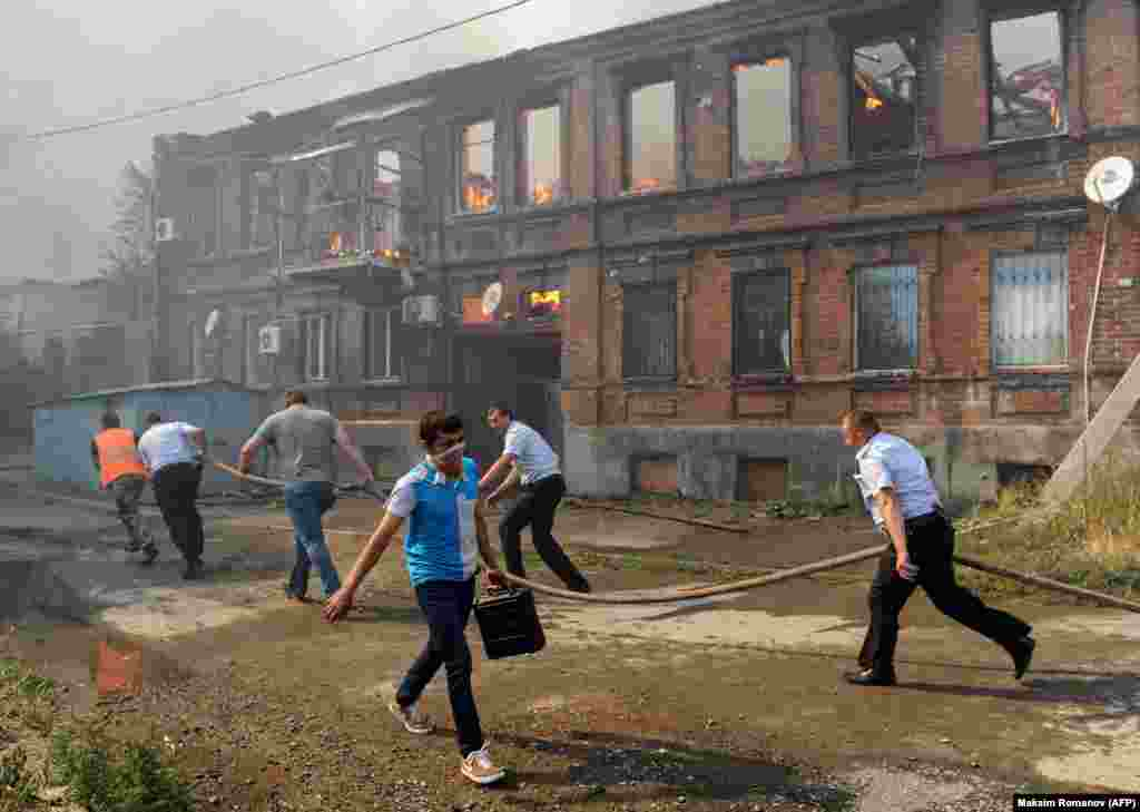 Police officers and municipal workers run with a hose as they attempt to extinguish a fire that engulfed a residential area in the southern Russian city of Rostov-on-Don on August 21. (AFP/Maksim Romanov)