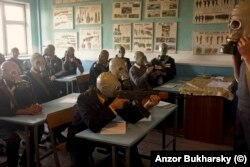 High-school students with a wooden Kalashnikov and real gas masks during a lesson in 2010