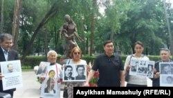 Гражданские активисты с портретами политзаключенных и репрессированных у памятника жертвам Голода. Алматы, 31 мая 2017 года.