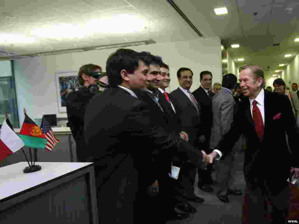Journalists from Radio Free Afghanistan shake hands with the president.