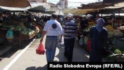 Илустрација: Луѓе се движат покрај тезги на пазар.