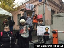 People gathered near a memorial plaque dedicated to Politkovskaya near the Novaya Gazeta offices to register their anger that whoever ordered her killing has not yet been found.