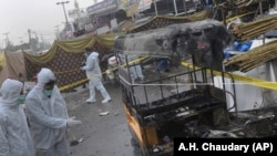 Pakistani investigators examine the site of bomb explosion in Rawalpindi on December 4 that killed one person and wounded seven outside a grocery store at the Pir Wadhai bus terminal.