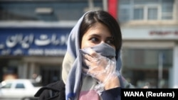 An Iranian woman covers her face, following the coronavirus outbreak, as she walks in Tehran, March 5, 2020