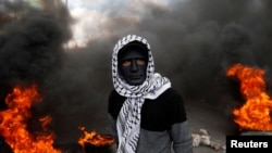 A Palestinian demonstrator stands near burning tires during clashes with Israeli troops.