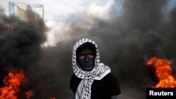 İsrail askerleri ile çatışmalar esnasında filistinli numayışçı yanğan avtomobil şinaları yanında tura