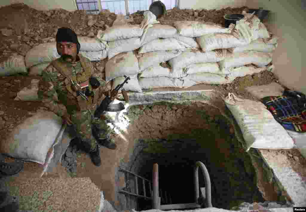 A member of the Iraqi security forces stands next to a tunnel used by IS militants during a battle near Mosul. Many of IS's strongholds are honeycombed with tunnels, allowing the group's fighters to disappear from one position and pop up elsewhere.