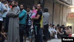 Люди стоят в очереди за хлебом в одном из пригородов Алеппо