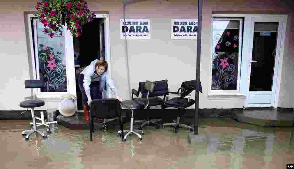 A woman attempts to save furniture from her flooded office in Banja Luka, western Bosnia-Herzegovina.