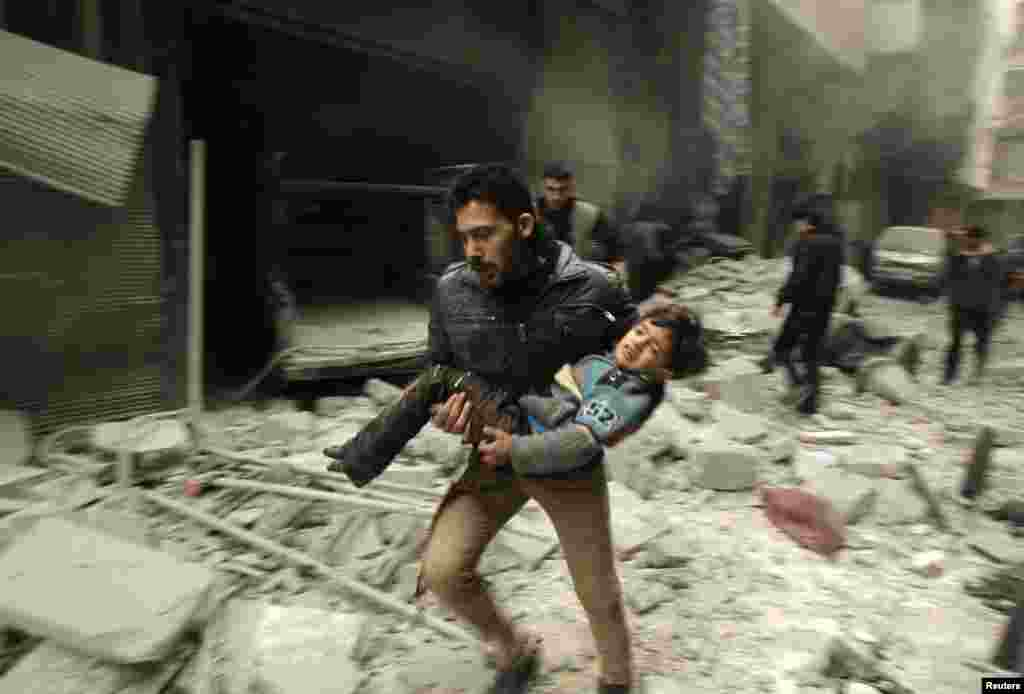 A man runs as he carries a child who survived what activists say was an air strike by forces loyal to Syrian President Bashar al-Assad in Aleppo on January 21. (Reuters/Ammar Abdullah)