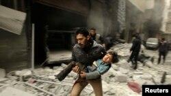 صورة لسوري في حلب ينقذ طفلاً من موقع تعرض لقصف جوي - 21 كانون الثاني 2014