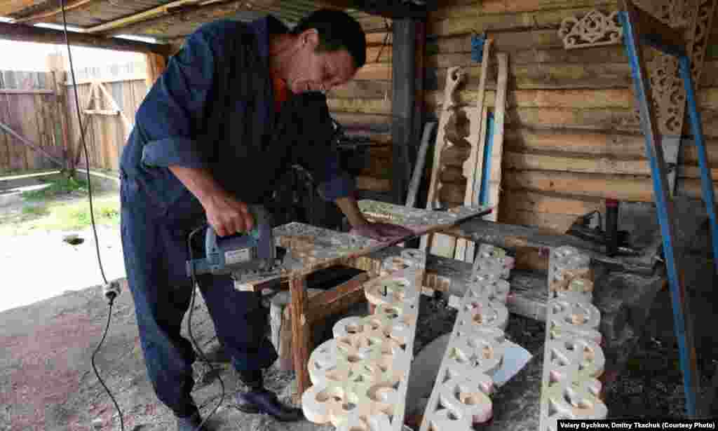 A local carpenter produces traditionally ornate wooden window frames.