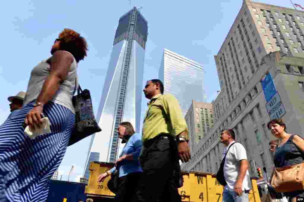 With the redevelopment well under way, lower Manhattan is bustling once again. Here, people walk past the One World Trade Center tower on August 8, 2012.