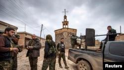 عناصر من قوات حماية الشعب الكردية تقف امام كنيسة آشورية في قرية تل جمعة 25 شباط 2015
