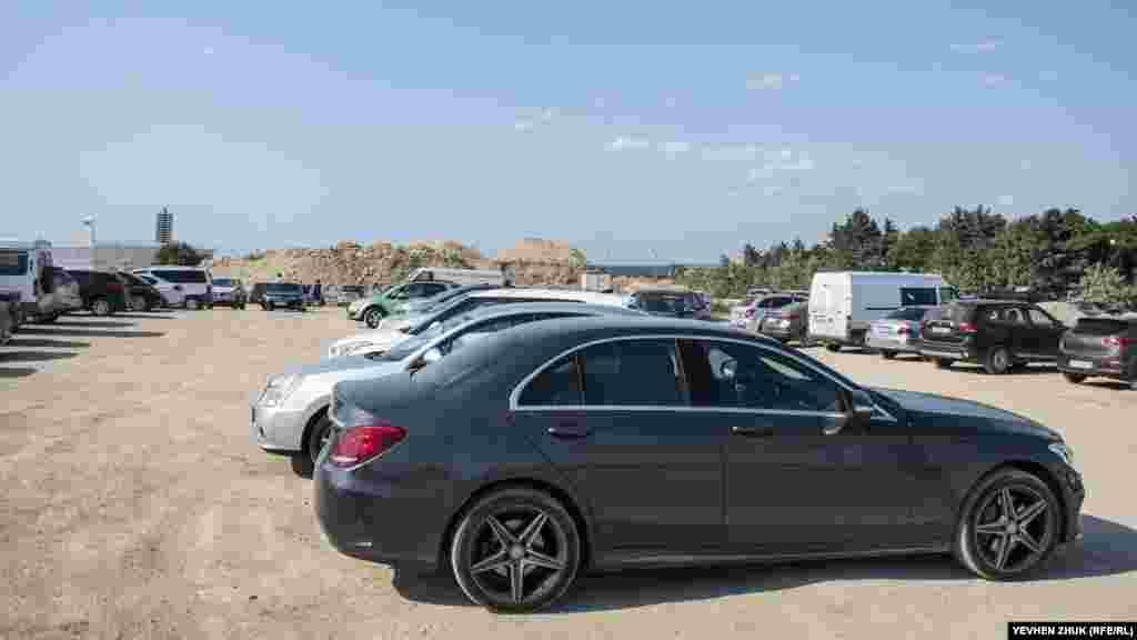 Імпровізована парковка автомобілів поряд з купами будівельного сміття
