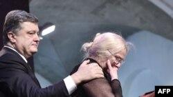 Президент Украины Петр Порошенко утешает родственницу посмертно награжденного погибшего участника акций на Майдане медалью Героя Украины. Киев, 20 февраля 2015 года.