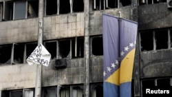 Bosnia-Herzegovina -- A Bosnian flag and a sign flutter in front of a burned government building in Tuzla February 8, 2014.