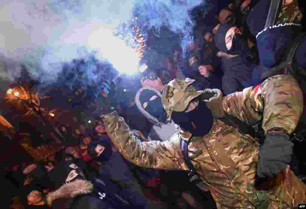 "Ukrainian far-right activists throw smoke bombs at police during a protest in front of the presidential office in Kyiv. Protesters were demanding the release of ""all jailed political prisoners."" (AFP/Sergei Supinsky)"