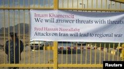"""Уран байыту кешенінің қақпасына ілінген плакатта аятолла Хаменеидің """"Қоқан-лоқыға қоқан-лоқымен жауап береміз"""" деген сөздері жазылған. Исфахан, 15 қараша 2011 жыл"""