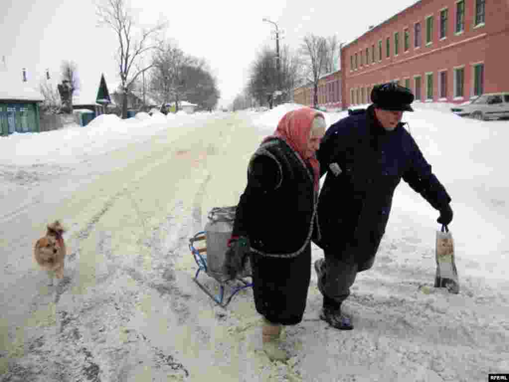 Residents pull a can of water on a sled in the Belarusian town of Talachyn.