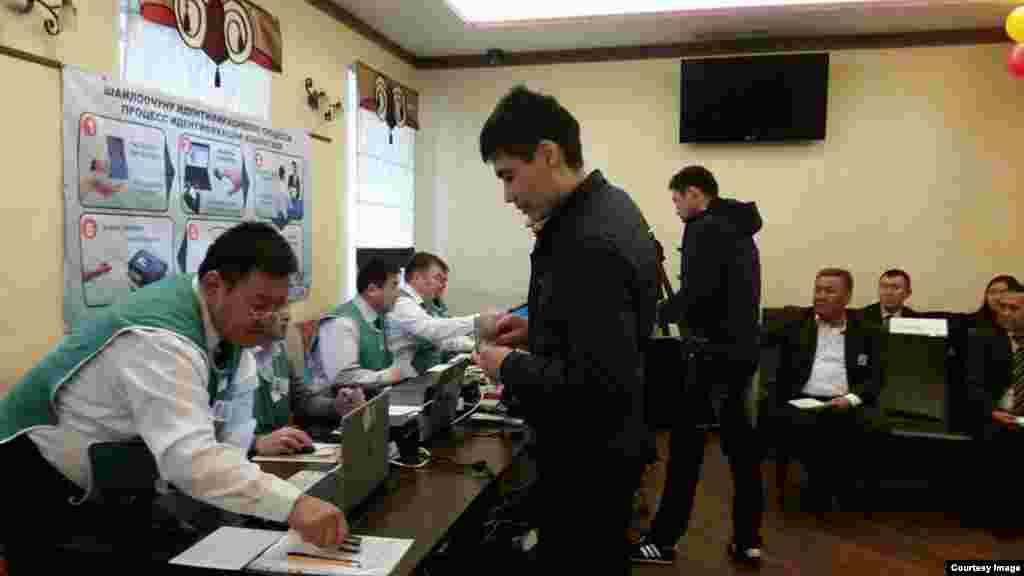 Ресей астанасында орналасқан 9001-сайлау учаскесінде Қырғызстан парламенті сайлауына дауыс беруге келген азаматтар сайлау бюллетенін алып тұр. Мәскеу, 4 қазан 2015 жыл.