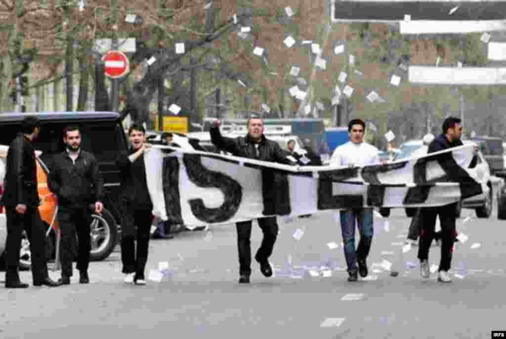 تظاهرات کنندگان با پارچهای نوشتهای که بر روی آن کلمه «استعفا» دیده میشود