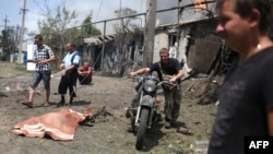 Local residents pass the covered body of an apparent civilian casualty in the village of Stanitsa Luhanskaya, in the eastern industrial province of Luhansk, on July 2.