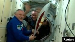 Космонавт Федор Юрчихин (сол жақта) олимпиада факелін ұстап тұр. Оған оны космонавт Михаил Тюрин 7 қараша күні тапсырды. Халықаралық ғарыш станциясы, 7 қараша 2013 жыл.