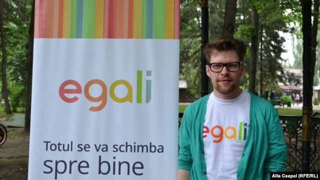 Gay activist Artiom Zavadovsky stands by a poster for Egali.md, a web platform and a video campaign in support of LGBT and gay Moldovans.