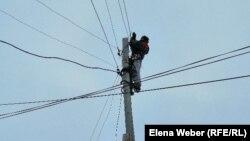 Қарағанды облысы Жаңаарқа ауданында электр бағанына шығып тұрған жұмысшы.