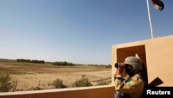 An Iraqi border policeman looks through a pair of binoculars near the Iraqi-Syrian borders at the Abu Kamal-qaim border crossing, the main border post between Iraq and Syria, September 8, 2012