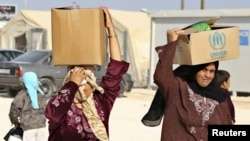 Syrian refugees carry aid and rations at the Zaatari refugee camp in the city of Mafraq, Jordan. (file photo)