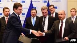 Газ туралы келісімге қол қойылған соң Ресей мен Украина энергетика министрлері - Александр Новак пен Юрий Продан (алдыңғы қатарда) қол алысып тұр. Брюссель, 30 қазан 2014 жыл.