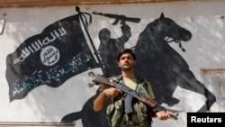 """Боец отряда """"Свободной Сирийской Армии"""", поддерживаемой Турцией и США и воюющей против курдов и ИГИЛ, на фоне отбитого у джихадистов здания с их символикой. Город Джараблус, 31 августа"""