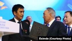 Дуйшонкул Шаматов, потомок Кузебая Куранова, вручает рукопись президенту РК Нурсултану Назарбаеву.