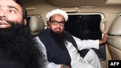 FILE: Hafiz Saeed, leader of the Jamaat-ud-Dawa (JuD) organisation Hafiz Saeed (R) leaves in a car after being detained by the police in the eastern city of Lahore in January.