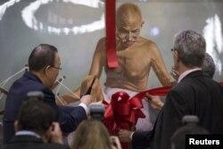 Генеральный секретарь ООН Пан Ги Мун перерезает ленту на картине с изображением Махатмы Ганди на мероприятии по случаю Международного дня без насилия