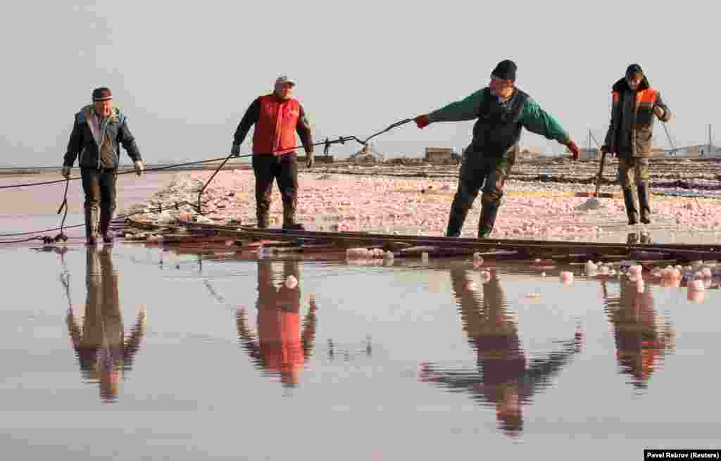 Laborers work on a partially drained lake bed.