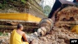 Буддист у развалин пагоды на следующий день после землетрясения в Мьянме, 25 марта 2011