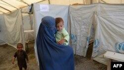 Женщина с детьми в лагере для беженцев в Кабуле. 20 июня 2013 года.