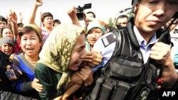 Ұйғыр әйелі полицейді жібермеуге тырысып жатыр. Қытай, Үрімжі, 7 маусым 2009 жыл.