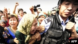 Ethnic Uyghur women grab at a riot policeman as they protest in Urumqi, Xinjiang province, on July 7.