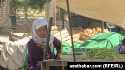 Türkmenistanyň bazarlarynyň birinde noýwa satýan zenan.