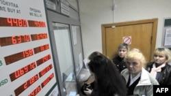 People exchange money inside an exchange office in Minsk