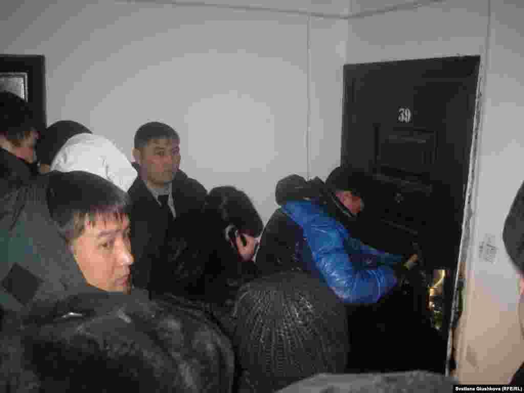 """В Астане началось выселение нескольких десятков дольщиков, имеющих более одной квартиры. В их квартиры вселяют дольщиков, не получивших жилья. Власти исполняют постановление правительства 2010 года, суть которого сводится к приципу «одно жилье — в одни руки». На фото: в присутствии судебных исполнителей и полицейских взламывают дверь квартиры дольщика в ЖК """"Европейский"""". Астана, 30 января 2013 года."""