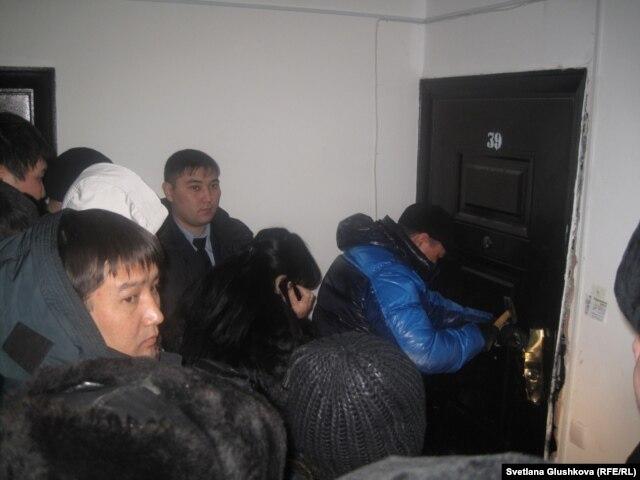Судебные исполнители производят вскрытие квартиры с целью ее передачи от одного дольщика другому. Астана, 30 января 2013 года.
