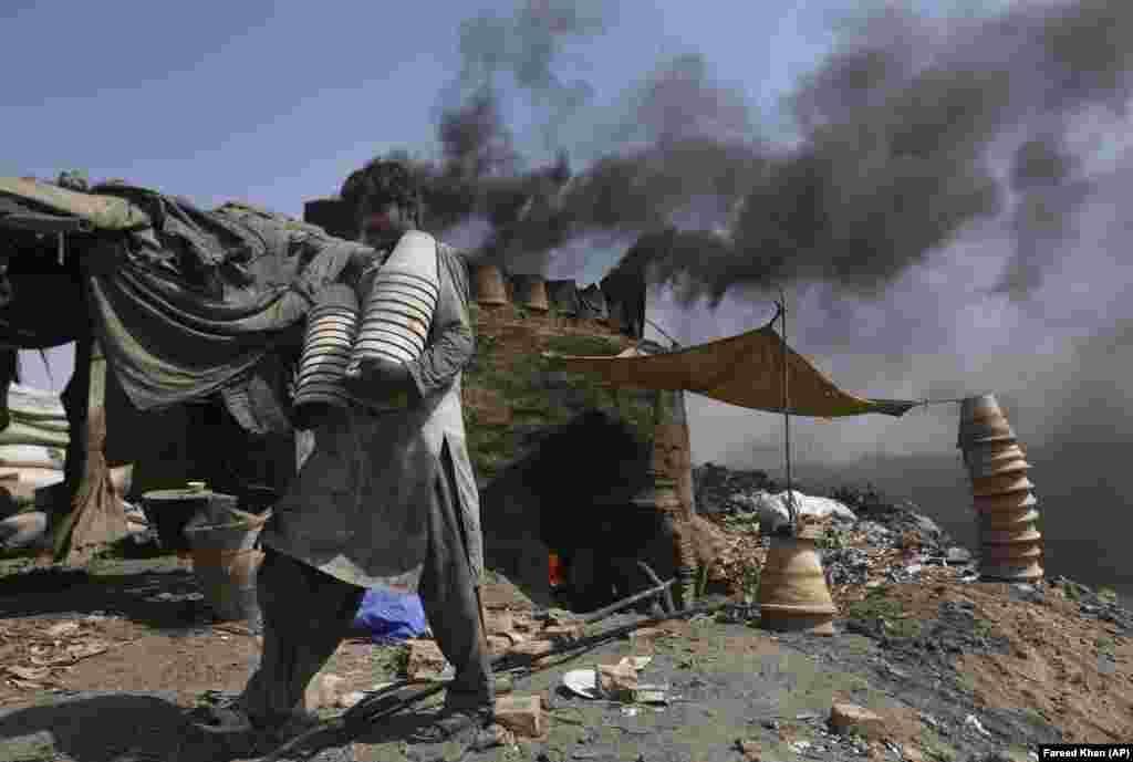 A Pakistani potter carries clay pots at a workshop in Karachi. (AP/Fareed Khan)