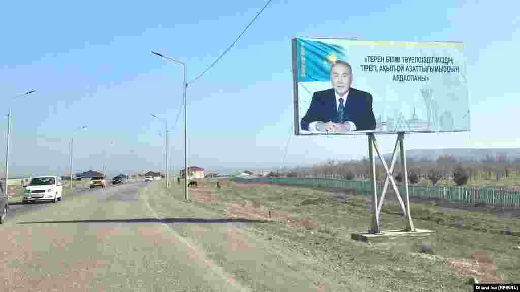 Түркістаннан Кентауға баратын жол бойында тұрған Қазақстанның экс-президенті Нұрсұлтан Назарбаевтың суреті бар билборд.