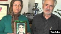پدر و مادر سعید زینالی، عکس فرزندشان را در دست دارند.
