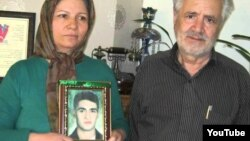 Akram Neghabi, standing next to her husband, Hashem Zeinali, holds a photograph of her son Saeed Zeinali, who has been missing since 1999.